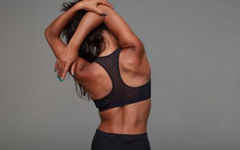 Back view of young athletic dark skinned curly brunette female stretching her hands while posing over grey background in black sporty top. Fitness female model